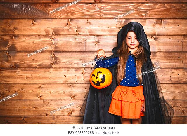 Laughing funny child girl in a witch costume in halloween
