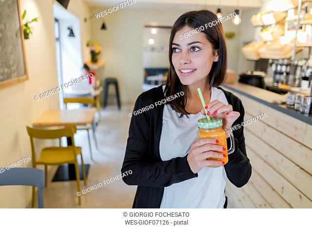 Portrait of a young woman with a smoothie in a cafe