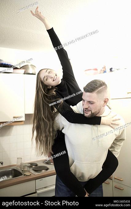 happy girlfriend piggyback on boyfriend in kitchen
