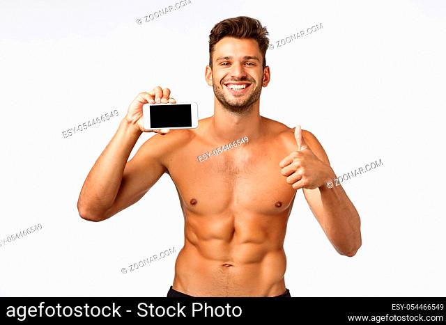 Charming bearded shirtless, handsome sportsman with six-packs, masculine perfect body, holding smartphone horizontally, show thumbs-up in approval, smiling