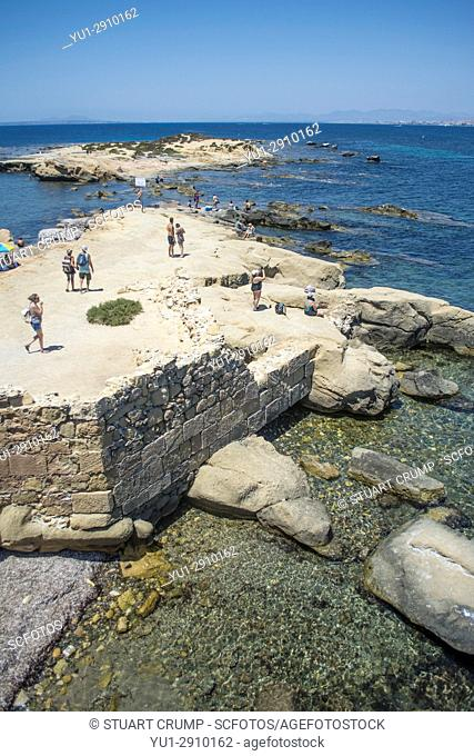 Tourists on the rocky coastline on the island of Tabarca Spain