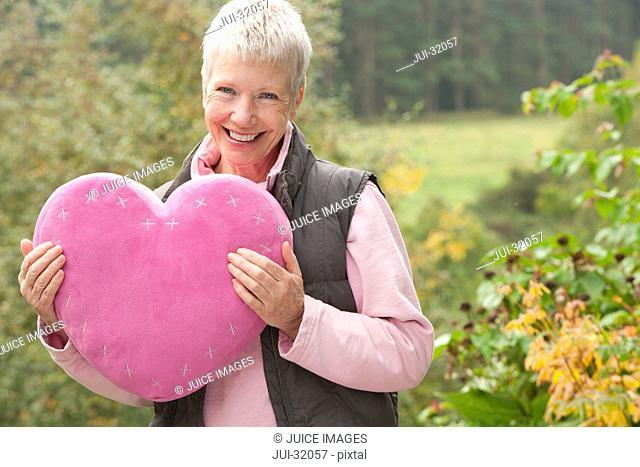 Portrait of smiling woman holding heart-shape pillow in garden
