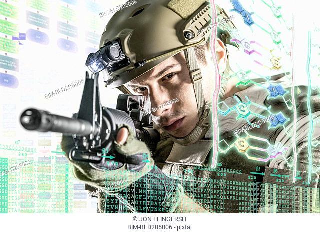 Caucasian soldier pointing gun at illuminated holograms