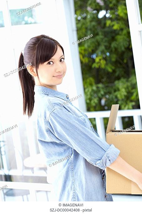 Young woman carrying a cardboard box