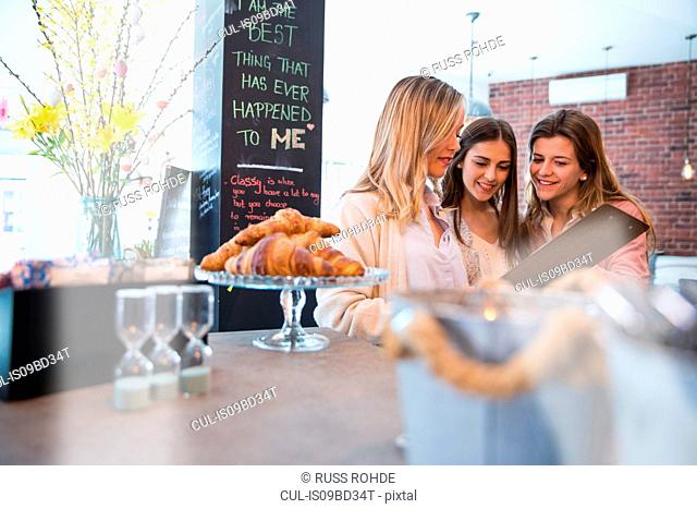 Three female friends, looking at menu in cafe