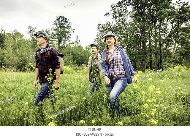 Young adults and teen boy wearing flat caps walking in tall grass smiling