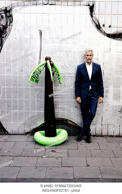 Mature businessman outdoors with inflatable palm tree