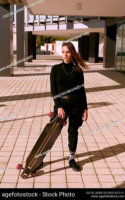 Young skater girl dressed in black poses with her skateboard in