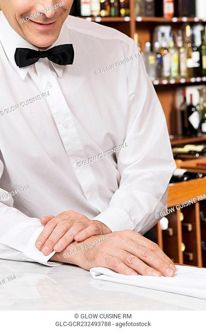 Waiter leaning against a bar counter