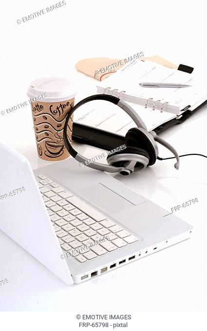 Laptop, headset, coffee cup and a date book