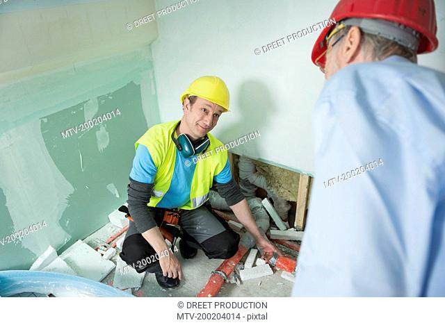 Architect and construction worker at construction site of new building