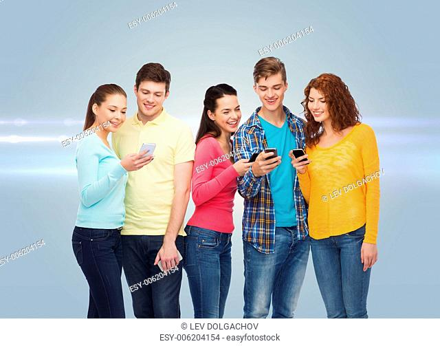 friendship, technology and people concept - group of smiling teenagers with smartphones over gray background with laser light