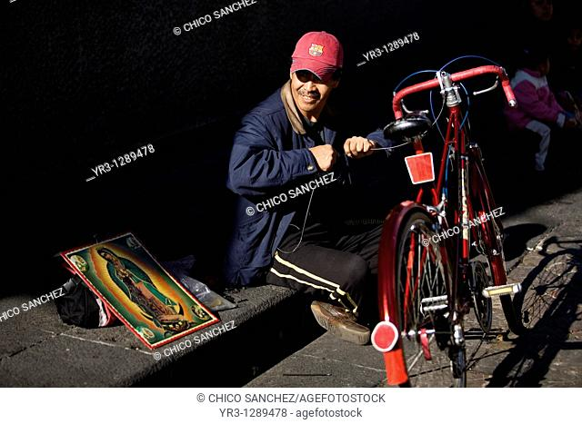 A man repairs his bicycle outside the Our Lady of Guadalupe Basilica in Mexico City, December 9, 2010  Hundreds of thousands of Mexican pilgrims converged on...