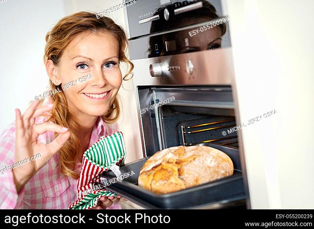 smiling woman takes out fragrant and crunchy bread from the oven in the kitchen