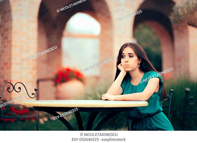 Disappointed girl sitting alone in a garden waiting a date