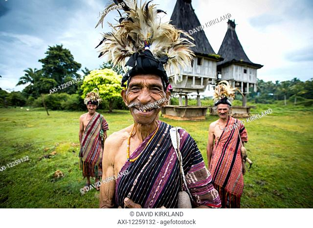 Group of men in traditional attire with sacred houses in the background; Lospalmos district, Timor-Leste