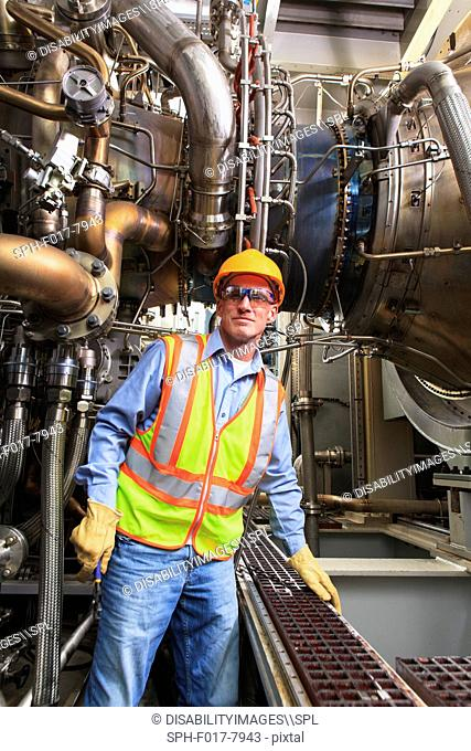 Engineer at fuel injection stage of gas turbine which drives generators in power plant while turbine is powered down