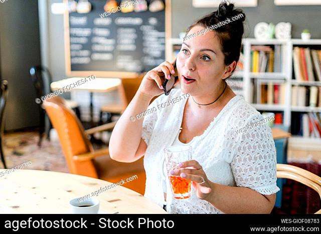 Voluptuous woman holding drink talking over mobile phone while sitting in restaurant