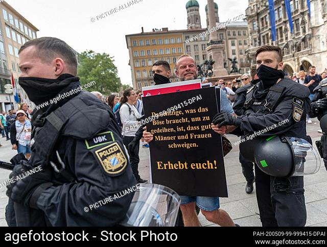 09 May 2020, Bavaria, Munich: Police officers take away a demonstrator with his poster, who had previously demonstrated in a crowd on Marienplatz