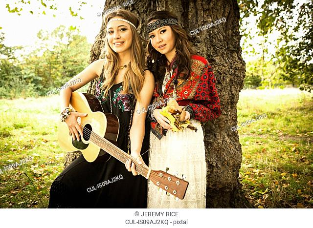 Hippy girls by tree with guitar