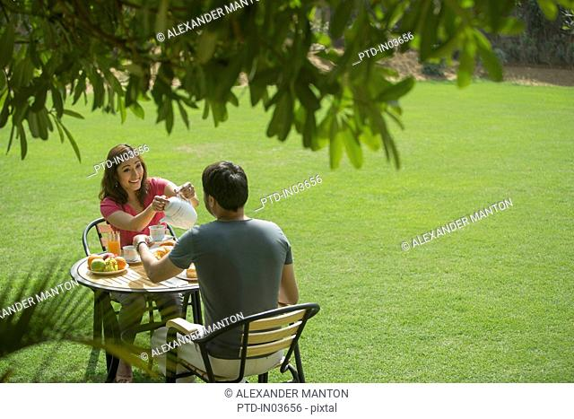 woman pouring coffee for man at table outside