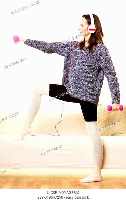 woman with dumbbells at home listening music