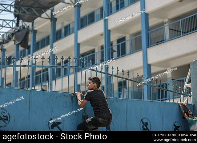 13 August 2020, Palestinian Territories, Al-Shati: Palestinian students climb the gate of a school run by the United Nations Relief and Works Agency for...