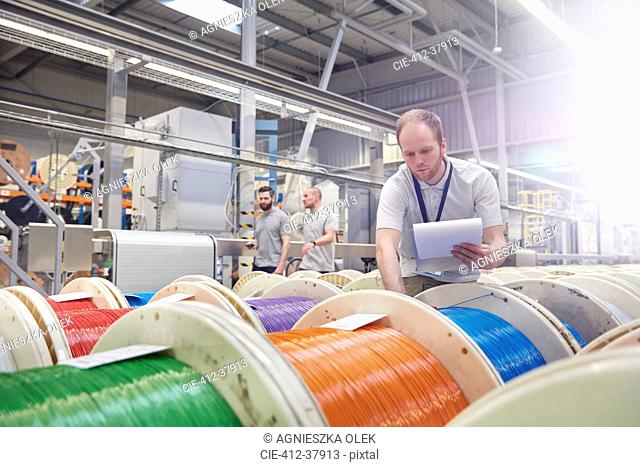 Male worker with clipboard checking multicolor spools in fiber optics factory