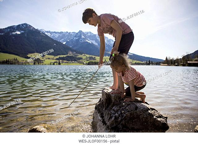 Austria, Tyrol, Walchsee, brother and sister playing in the lake