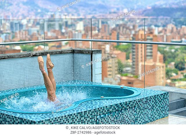 Ballerina immersed in a rooftop jacuzzi in Medellin