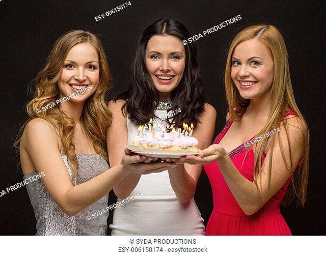 celebration, food, friends, bachelorette party and birthday concept - three smiling women holding cake with candles