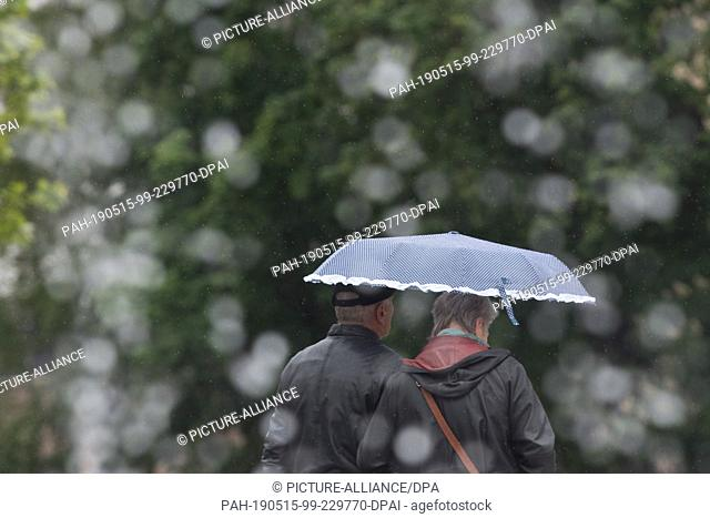 "15 May 2019, Saxony, Dresden: Passers-by walk under an umbrella behind the fountain """"Water Curtain"""" on the Postplatz. Photo: Sebastian..."