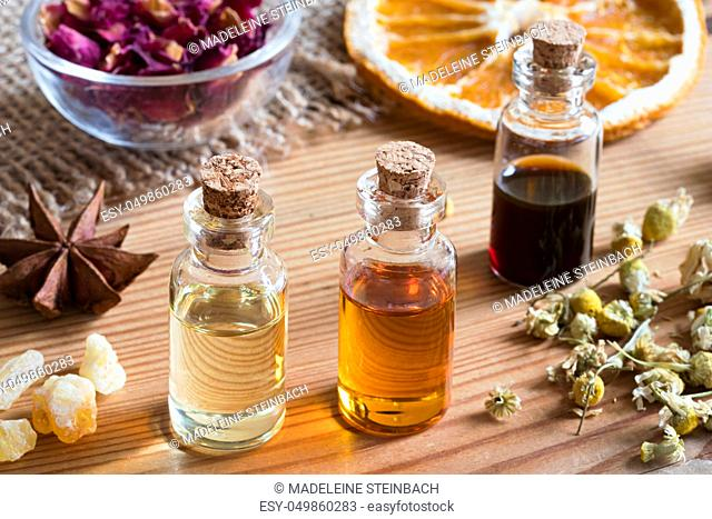 Bottles of essential oil with dried chamomile flowers, orange slices, frankincense and star anise on a wooden table