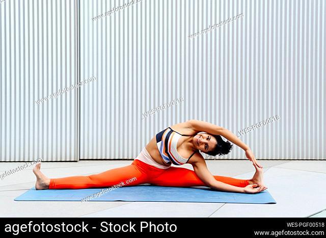 Female athlete stretching with wide legged in front of wall