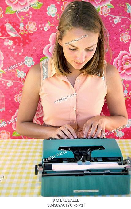 Adolescent girl using vintage typewriter