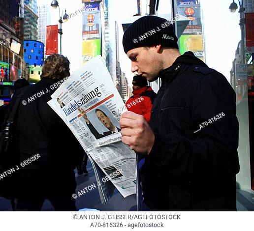 Man reading the Handelszeitung business paper. Times Square. New York City