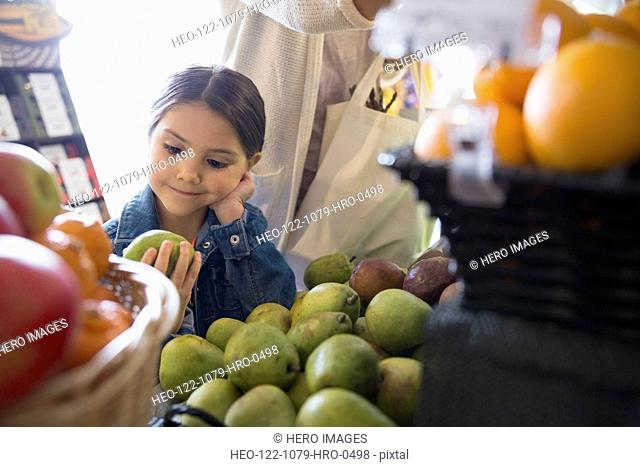 Girl looking at pear in market