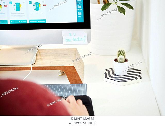 A workstation in an office, computer screen, keyboard and cactus plant. Over the shoulder view. Post it note saying R U time tracking?