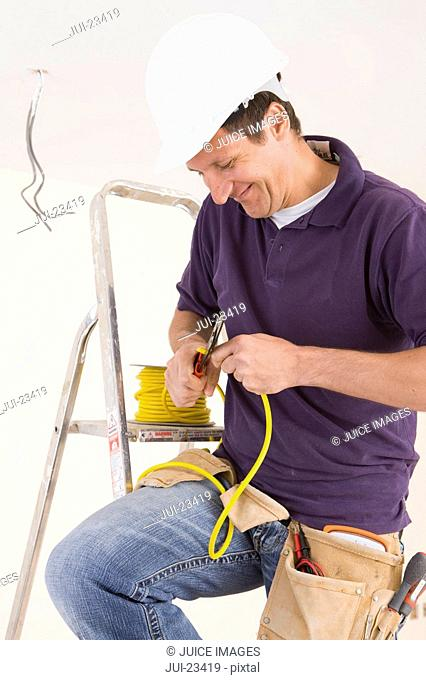 Electrician on ladder cutting cable