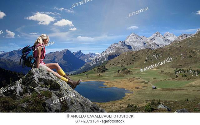 Woman watching an alpine lake, Lai da Vons, Canton of Graubünden, Switzerland