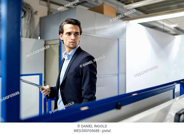 Businessman with tablet in a factory looking around