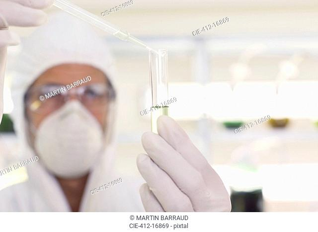 Scientist in clean suit using pipette and test tube in laboratory