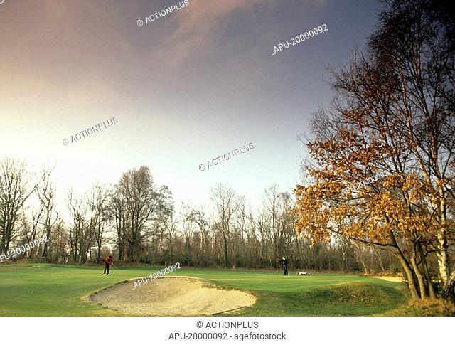 Golfers by a sand bunker on a golf course