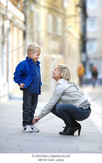Mother tying son's shoestring