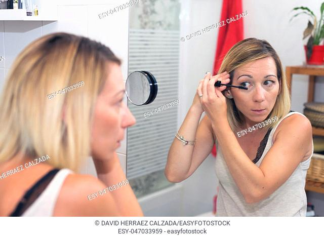 Beautiful blonde woman applying mascara on her eyelashes
