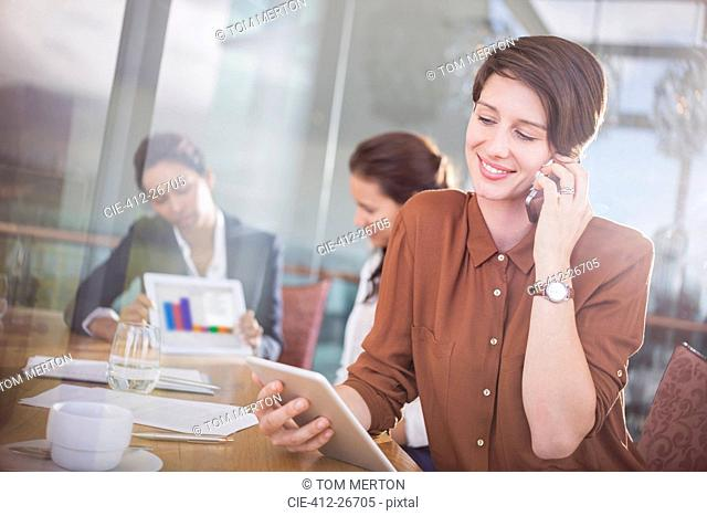 Businesswoman talking on cell phone and using digital tablet in office