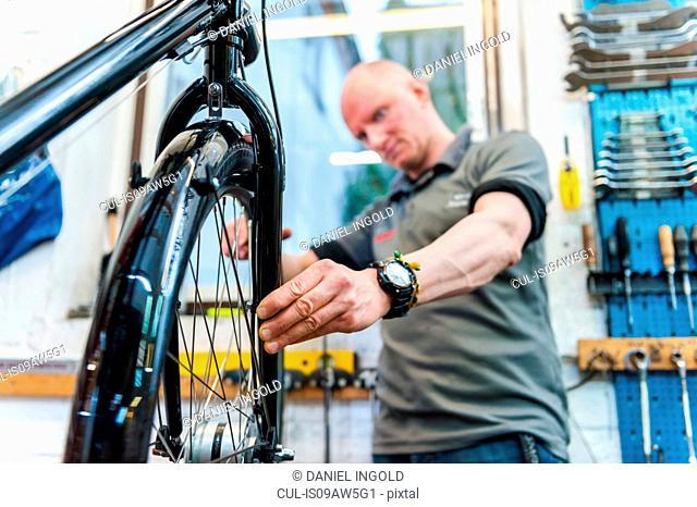 Mechanic repairing bicycle in workshop