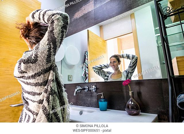 Young woman at home doing her hair in front of mirror