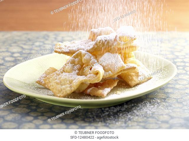 Faworki (Polish carnival pastries) being dusted with icing sugar