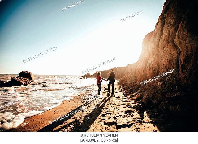 Mid adult couple holding hands on sunlit beach, Odessa Oblast, Ukraine